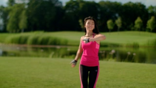 Happy woman dancing and turning on meadow at summer. Asian woman dancing outdoor in slow motion. Fitness girl having fun on sunny day. Asian girl dancing and smiling after workout