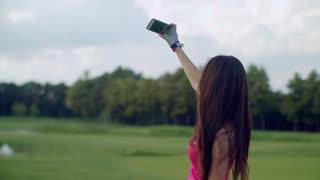Happy woman taking selfie outdoors. Sport woman taking selfie on smartphone in park. Selfie woman. Young woman posing to taking selfi photo. Asian girl selfie portrait on meadow