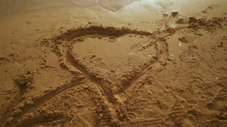Heart draw on sand. Sand background with heart shape. Closeup of heart on sand. Love concept. Close up of heart on sand beach. Heart symbol on sea beach. Love symbol. Heart sand. Beach heart