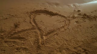 Heart sand. Heart drawing on sand beach. Panning from heart symbol on sand to sky over sea. Sea beach with heart on sand. Romantic background. Honeymoon vacation background
