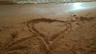 Heart shape on beach sand. Steady shot. Heart draw on sand beach. Panning from heart shape on sand to seascape view. Sea beach with heart on sand. Beach holidays. Romantic vacation