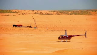 Helicopter in desert. Desert transport. Helicopter on sand in desert. Helicopter in extreme location. Herd of cows. Desert landscape with helicopter and cows near watering place. Desert safari on helicopter