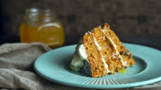 Honey pouring carrot cake piece. Pouring honey on sweet dessert. Dripping honey on homemade cake. Sweet pie with syrup. Dessert pie on plate. Serving dish