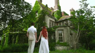 Honeymoon couple looking at beautiful country house. Fairytale house. Beautiful mansion exterior. Love couple near old country residence. Ancient building