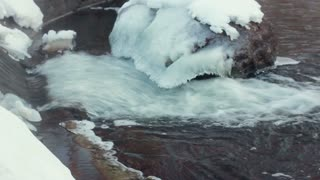 Ice covered stone. Water flowing near stone in winter. Closeup. Winter river. Icy rocks on winter river. Ice stone. Winter cold river. River rapids. Fast flowing river. Water motion. River flows