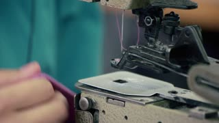 Female worker at sewing machine at textile factory. Tailor working witj industrial sewing machine. Tailor at clothing factory