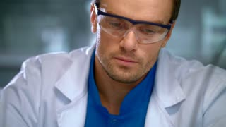 Laboratory worker face. Medical researcher working in lab. Young scientist thinking. Portrait of lab worker in safety glasses. Male chemist working. Closeup of lab man in white coat