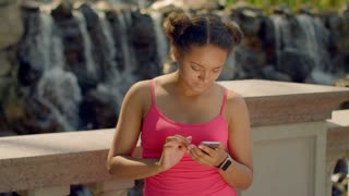 Latin girl using smartphone at park. African woman using phone outdoor. Digital lifestyle concept. Smart watch on hand. Girl phone. Young woman look phone. Afro american woman surfing internet