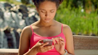 Latin woman looking at phone. Thoughtful woman face. Young woman using smartphone outdoors. Attractive woman reading sms on phone. Woman phone. Afro woman gesturing on phone. Internet addiction