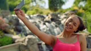 Latin woman taking selfie photo. Selfie woman. Closeup of african woman taking selfie at park in summer. Afro american woman taking photo with phone outdoor. Phone selfie. Woman smiling. Self portrait