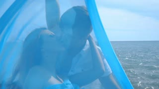 Love couple kissing. Happy woman kissing man behind blue cloth. Happy family. Romantic couple. Kissing couple. Couple in love kissing behind blue cloth. Romantic sea vacation. Romantic concept