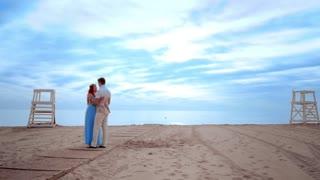 Love couple kissing on beach. Couple beach sunrise. Pregnant couple on blue sky background. Couple hugging on beach. Love couple on blue sky background. Romantic couple kissing