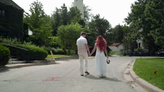 Love couple walking in park. Couple in love holding hands together. Back view of walking couple. Rear view of young people walk together. Man and woman in white clothing holding hands while walking