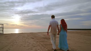 Love couple walking on sea beach at sunrise. Couple beach. People holding hands on sea beach. Couple walking on sand beach. Couple in love on vacations. Relationship concept. Romantic couple