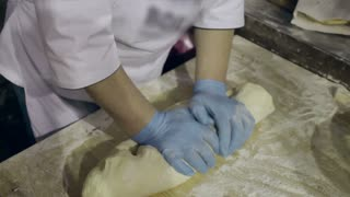 Making dough at kitchen. Chef hands kneading dough. Hands form raw dough. Baker cooking bread. Chef rolls dough. Woman prepares dough for homemade baking. Dough modeling. Cook forming dough