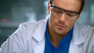 Male researcher studying liquid in glass flask at lab. Closeup of scientist man doing medical research at laboratory. Pharmacist analyzing substance in flask. Chemist doing pharmaceutical research