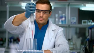 Male scientist conducting research in chemical lab. Scientist working with chemical liquid in research laboratory. Scientist filling test tubes with samples in laboratory. Scientist working in lab