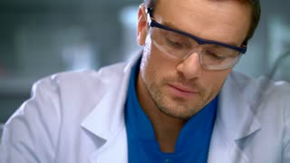 Male scientist in lab. Close up of scientist man looking at liquid in glass flask at laboratory. Scientist analyzing substance in flask. Scientist working with liquid at research laboratory