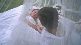 Man and red hair woman laying on white veil behind transparent cloth at park. Romantic couple relaxing behind white transparent veil. Close up of love couple resting outdoor in romantic decorations