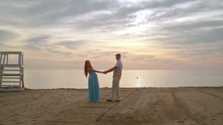 Man and woman holding hands on sea beach. Couple beach sunrise. Pregnant couple posing for photo session on beach at sunrise. Love couple on beach. Young couple on honeymoon vacation