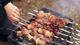 Man cook meat on skewers. Man hand turns grilled meat on mangal. Cooking picnic food. Controlling food preparation on grill. Grilling kebab on coals. Grill meat. Cook barbeque meat on grill. Shashlik