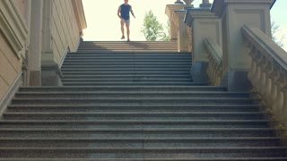Man jogging down stairs in slow motion. Man running down stairs. Running man on stone staircase. Man running down steps. Jogger runs downstairs. Man running on stairway. Fitness workout outdoor