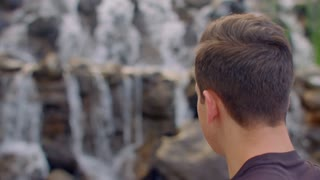 Man looking at waterfall. Closeup of man relaxing at nature. Rear view of young hiker looking at waterfall in spring. People and nature concept