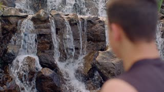 Man relaxing near waterfall. Relaxation concept. Closeup of mans head on background of falling water. Rear view of man looking at mountain waterfall. Man standing next to water falling over stones