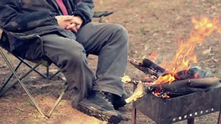 Man sitting on camp chair near bonfire. Outdoor recreation. Campfire in forest. Tourist resting near fire. Bonfire in camp. Rest in camping. Relax in forest. Relaxing near wood burning in mangal