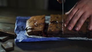 Man slicing cake on wooden table. Prepared chocolate cake pieces on kitchen. Chef cutting chocolate cake. Brownie cake slices. Sweet food. Delicious dessert. Cutting chocolate brownie