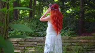 Man spying on redhead woman in green forest. Red hair woman in white dress at park at summer. Young woman in forest at sunny day