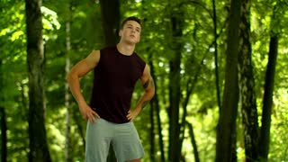 Man stretching outdoor. Fit boy doing stretching exercise at morning. Wellness concept and healthy lifestyle. Athletic man doing fitness exercises in park. Sport man doing fitness exercises