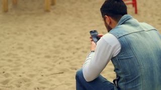 Man using smartphone sitting on playground. Mobile phone used by young guy for communication. Bearded man with smart phone. Modern lifestyle. Guy on playground use internet on smartphone