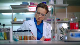 Medical researcher in medical research lab. Clinical research. Medical lab technician working in chemical laboratory. Lab doctor writing test result. Medical scientist working at the lab