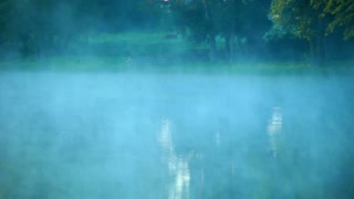 Mist over water. Fog over water surface. Foggy morning at lake. Morning mist over forest river. Dawn at forest lake. Green tree on riverbank