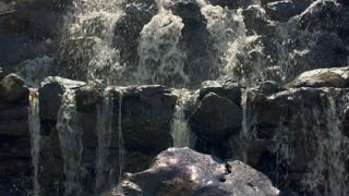 Mountain waterfall. Close up of water falling over stones in slow motion. Water streams falling over rocks in sunlight. Rushing water in slow motion. Water splashes. Waterfall mountain