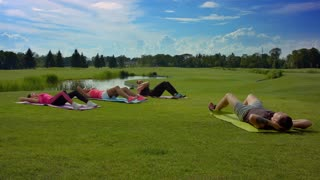 Multi ethnic people group doing sit-ups. Outdoor fitness class. Fitness workout outdoors. People group doing crunch exercise. Outdoor fitness training on grass. Athletic man showing exercise for women