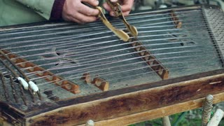 Musician play on traditional cimbalom. Musical instrument. Traditional music instrument. Man fingering string cimbalom instrument with sticks. Dulcimer music stringed by musician