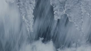 Nature background. Small waterfall in winter. Water flowing in winter. Fast water flow. Flowing water. Closeup. Icicles and running water. Icy waterfall close up. Abstract background. Water splashes