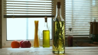 Olive oil bottle on kitchen table. Extra virgin olive oil with rosemary on kitchen background. Dolly shot of bottle with olive oil in glass bottle at kitchen. Rosemary herb. Cooking ingredients