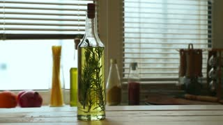 Olive oil bottle on wooden table. Extra virgin olive oil with rosemary herb on kitchen background. Rosemary herb in olive oil bottle. Greek food ingredient. Food product. Cooking ingredient