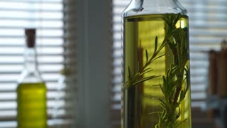 Olive oil with rosemary. Rosemary herb falls in olive oil bottle. Closeup of extra virgin olive oil in glass bottle at kitchen background. Italian food ingredient. Ingredient of greek food