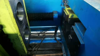 Operating the machine. Manufacturing process. Production line at manufacturing plant. Manufacturing of metal pipe