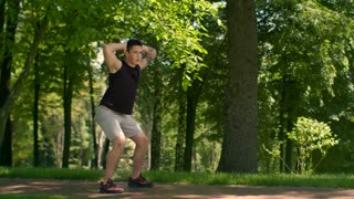 Outdoor fitness. Fitness man workout at park. Man doing squats. Fit man crouch in slow motion. Fitness man in sportswear doing fitness exercise. Sporty guy training. Boy doing sport exercise outdoor
