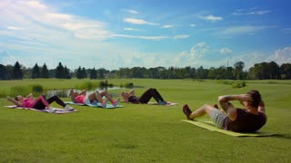 Outdoor fitness group doing sit up exercise. People group doing sit ups. Fitness people outdoors. Group of people exercising in summer park. Fitness instructor showing exercise for women on grass