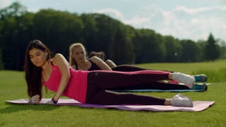 Outdoor group exercise in summer park. Multi ethnic sport group doing leg exercise on yoga mat. Fitness women doing leg lifts outdoors. Pretty girls doing leg raises in park. Outdoor fitness class