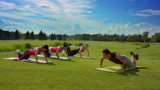 Outdoor group push ups. Group of people push ups outdoors. Fitness women group pushing with fitness instructor at sunny day. People group doing push up exercises outdoors. Fitness class outdoor