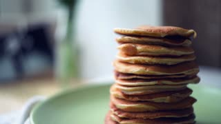 Pancakes stack on green plate at kitchen table. Close up of sweet american pancakes. Panning on dessert food baked for morning breakfast. Dessert meal at pancakes day. Closeup of homemade pancakes