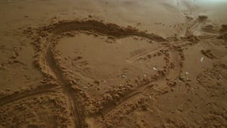 Panning from heart symbol on sand to seascape view. Sea beach with heart shape on sand. Romantic background. Love symbol on beach sand. Honeymoon vacation. Romantic sea view
