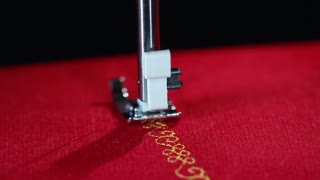 Pattern embroidered on fabric with modern sewing machine. Sewing needle stitching in slow motion. Household appliance. Detail of electric sewing machine